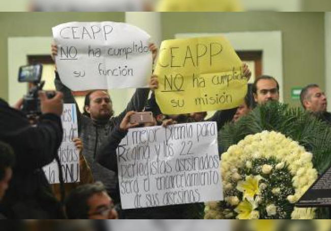 Comunicadores muestran pancartas hoy junto a una corona de flores y una placa con los nombres de los informadores muertos en el estado de Veracruz (México). EFE