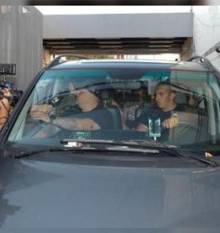 El exfutbolista argentino Diego Maradora (i-atrás, parcialmente cubierto) fue registrado este viernes al responde preguntas de la prensa, desde el interior de un vehículo, mientras salía de la Clínica Olivos, en Buenos Aires (Argentina). EFE
