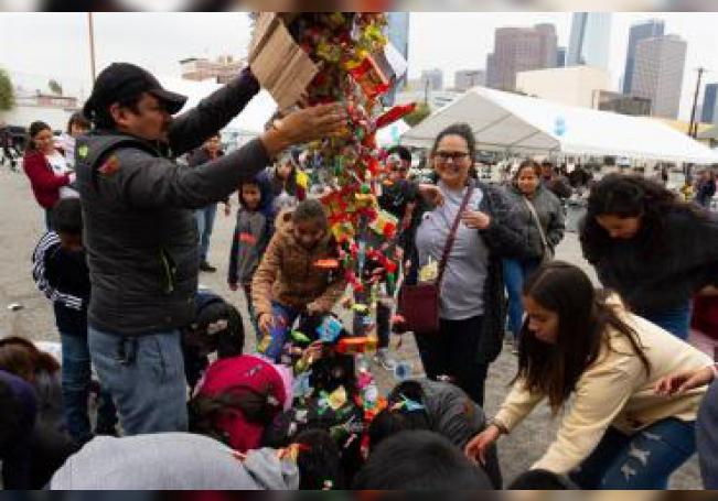 AME4192. LOS ÁNGELES (ESTADOS UNIDOS), 05/01/2019.- Un grupo de menores indocumentados recoge dulces de una piñata durante la celebración del Día de los Reyes Magos hoy, en Los Angeles, CA (EE.UU.). Cerca de un centenar de menores indocumentados que ingresaron a Estados Unidos sin compañía de un adulto celebraron hoy en Los Ángeles (California) el Día de los Reyes Magos, un descanso en medio de la