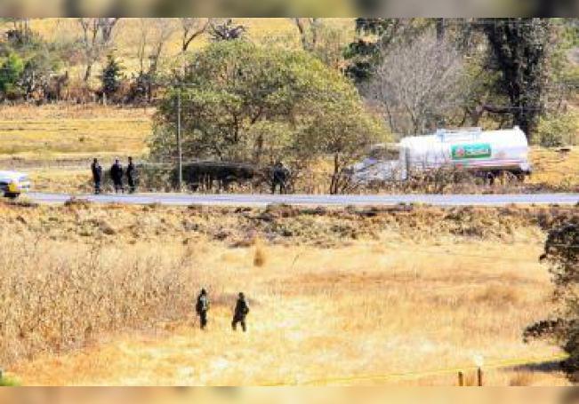 Militares montan guardia el viernes 24 de diciembre de 2010, en la zona donde las autoridades mexicanas controlaron una fuga de gasolina causada por una toma clandestina de combustible, en el municipio de Ahuazotepec, en la Sierra Norte de Puebla (México), el mismo estado donde hace cinco días otra fuga de petróleo causó un incendio y una explosión que mató a 29 personas e hirió a 52. EFE/Archivo