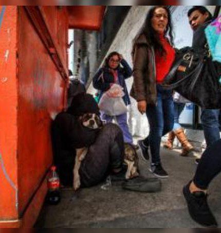 Fotografía del 31 de mayo de 2019, de varias personas que caminan junto a un migrante en condición de indigencia que abraza a su perro en una calle de Tijuana (México). La presión migratoria y la pobreza han llevado a un aumento de las personas en situación de calle en la fronteriza ciudad mexicana de Tijuana, impactando sobre el gasto de la ciudad y generando problemas entre comerciantes, según d