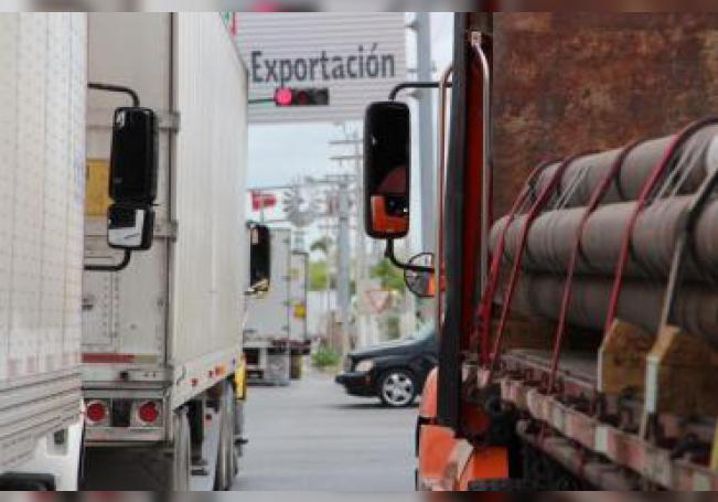 Camiones mexicanos que transportan principalmente productos automotrices esperan su turno para accerder a Estados Unidos, por el Puente Internacional Ignacio Zaragoza, en Matamoros, Tamaulipas (México). EFE/Archivo