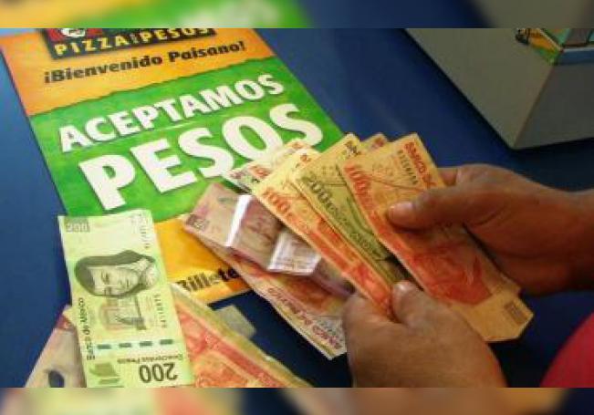 Un hombre cuenta unos pesos mexicanos, el lunes 3 de agosto 2009, en Chicago, Illinois. EFE/Archivo