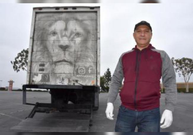 El mexicano Arnulfo González posa frente a la figura de un león que dibujó en la puerta trasera de su camión el pasado 15 de junio, en el estacionamiento del Centro comercial Puente Hills, en City of Industry, California (EE.UU.). EFE