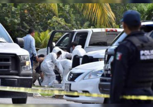 Peritos forenses inspeccionan la zona en la que hubo un enfrentamiento entre bandas rivales este sábado, en Cancún (México) y que dejó tres muertos y un herido según informaron las autoridades locales. EFE/Archivo