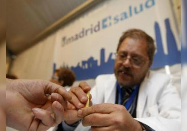 """Un médico saca una muestra de sangre a un asistente a la celebración del Día Mundial de la Diabetes, que se celebró bajo el lema """"Prevención y educación en diabetes"""". EFE/Archivo"""
