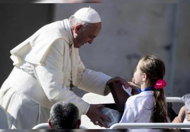 El papa Francisco saluda a una niña a su llegada a la audiencia general del papa en la plaza de San Pedro en el Vaticano, este miércoles. EFE