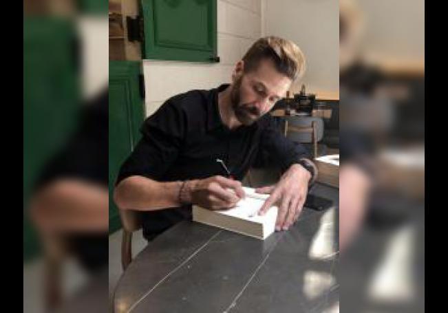 """El escritor Rodrigo Costoya Santos firma un ejemplar de su novela en español """"Portosanto"""" este lunes en Nueva York. EFE/Helen Cook"""