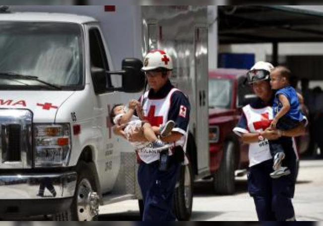 Socorristas de la Cruz Roja de México, llevan en brazos a dos niños intoxicados por comer pollo con chilaquiles. EFE/Elizabeth Ruiz