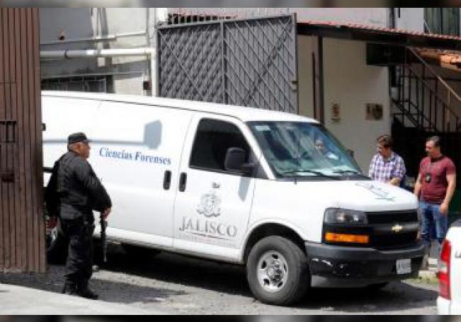 Agentes ministeriales resguardan este lunes una domicilio en la que fueron halladas 6 personas muertas y 4 lesionados en una finca localizada en la ciudad de Zapopan, estado de Jalisco (México). EFE/Francisco Guasco