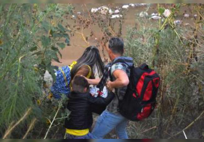 Una familia de migrantes centroamericanos cruzan este martes el Río Bravo, en ciudad Juárez, en el estado de Chihuahua (México). En una de las zonas más pobres de la mexicana Ciudad Juárez, donde se encuentran las compuertas del Río Bravo o río Grande, frontera natural entre México y Estados Unidos, la Patrulla Fronteriza estadounidense disparó gas pimienta a algunas personas que se bañaban en el