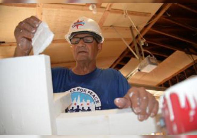 El carpintero retirado Greg Zanis pinta una de las cruces de madera que fabrica para honrar la memoria de víctimas de tiroteos masivos en Estados Unidos este 19 de agosto, en su taller de Aurora, Illinois (EE.UU.). EFE/ Enrique García Fuentes