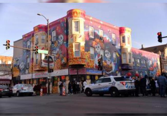 Unas personas asisten a la inauguración del mural realizado por la artista Elizabeth Reyes este viernes en La Villita, el barrio mexicano de Chicago (Illinois, EE.UU.). EFE/Enrique García Fuentes