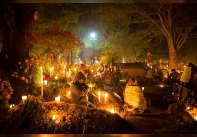 Decenas de personas velan en la madrugada de este viernes a sus muertos a la espera de su regreso, en un cementerio de Atzompa, en el estado de Oaxaca (México). EFE/ Arturo Velázquez