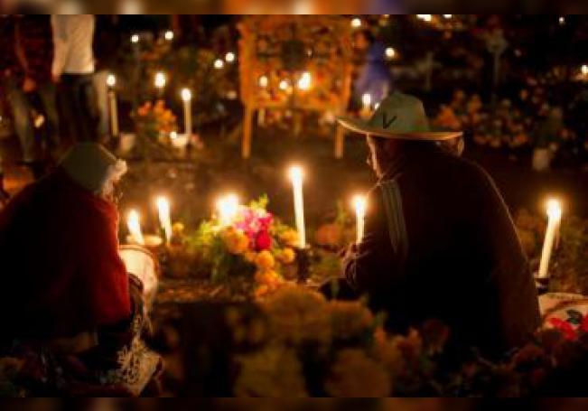 Pobladores hacen la velada a sus muertos en el panteón municipal y les ofrendan frutas y comida preparada que en vida gustaban consumir, la madrugada de este sábado, en la comunidad de Tzintzuntzan, en el estado de Michoacán (México). EFE/Luis Enrique Granados