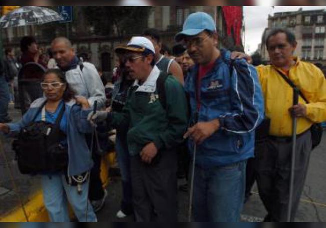 """Una familia de invidentes protesta el 22 de agosto de 2007, en el Zócalo en Ciudad de México, para exigir al gobierno que les permita continuar trabajando en las estaciones del sistema de transporte colectivo """"Metro"""". EFE/Marcos Delgado/Archivo"""