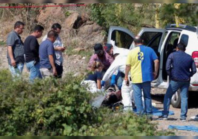 Expertos forenses laboran en el levantamiento de cadáveres de siete personas halladas sin vida en 3 vehículos en una brecha de la localidad de Tonalá, estado de Jalisco. EFE/ Francisco Guasco/Archivo