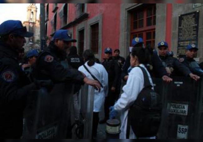 Miembros de la policía permiten el acceso de peritos forenses a la zona donde se presentó un tiroteo este sábado, en Ciudad de México (México). EFE/Madla Hartz