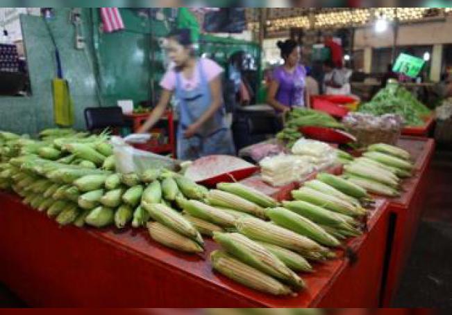 Fotografía de archivo del 10 de octubre de 2017 muestra a una mujer que vende mazorcas de maíz en un mercado de la Ciudad de México (México). EFE/Sáshenka Gutiérrez/Archivo