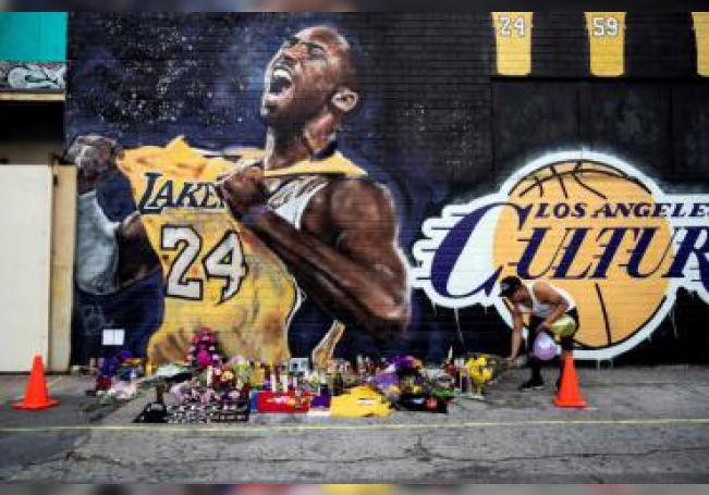 A man leaves flowers at a makeshift memorial in front of a mural of late Los Angeles Lakers guard Kobe Bryant near the Staples Center, home of the Los Angeles Lakers, in Los Angeles, California, USA, 27 January 2020. EFE/EPA/Etienne Laurent