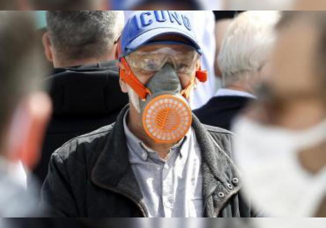 Una hombre camina entre la multitud con una máscara.