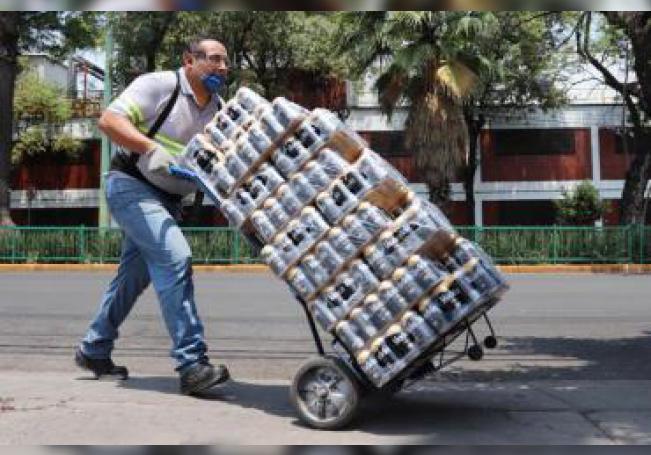 Un trabajador de la empresa mexicana Grupo Modelo traslada paquetes de cervezas para su venta en tiendas de la Ciudad de México (México). EFE/José Pazos/Archivo