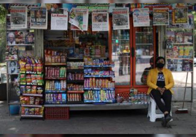 """Una mujer vuelve a abrir su puesto de venta de periódicos y dulces en un parque, este lunes, durante la """"nueva normalidad"""" decretada en la Ciudad de México, (México). EFE/ Sáshenka Gutiérrez"""