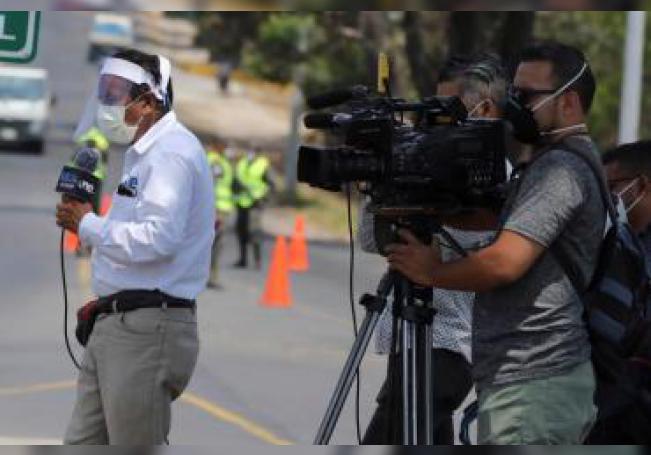 El periodista hondureño Víctor Rodríguez usa medidas de bioseguridad mientras informa en directo sobre la situación del avance del coronavirus). EFE/ Gustavo Amador/ Archivo