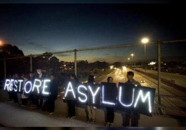 Activistas de grupos de derechos humanos sostienen carteles luminosos en los que reclaman que se reactive el asilo para los inmigrantes, en un paso elevado de la autopista junto a la frontera entre México y Estados Unidos en San Diego, California. EFE/EPA/DAVID MAUNG/Archivo