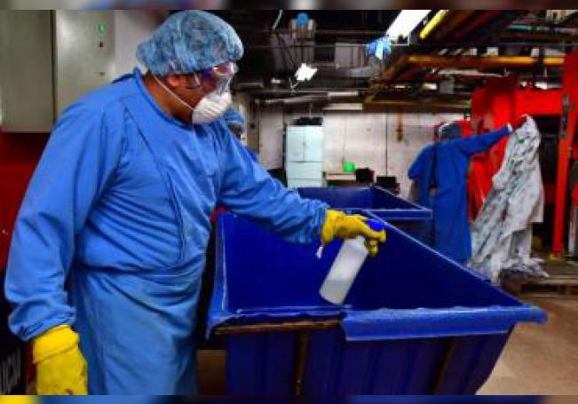 Empleados de la lavandería del Hospital Juárez realizan labores de desinfección, el martes, en Ciudad de México.