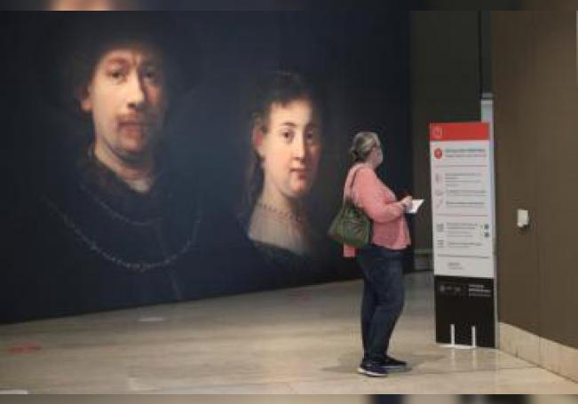 Una mujer lee atentamente un cartel informativo que recuerdan a los visitantes las medidas de higiene y distanciamiento a la entrada del Museo Thyssen-Bornemisza en Madrid. EFE/Rodrigo Jiménez