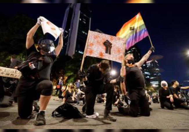 Jóvenes vestidos de negro y con velas encendidas y pancartas se hincan hoy jueves, frente a la Embajada de EEUU en la Ciudad de México (México). EFE/José Méndez