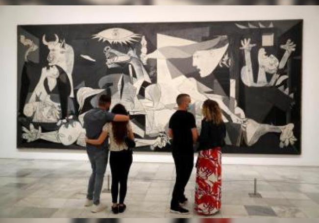"""Varias personas observan """"El Guernica"""" de Pablo Picasso en el museo Reina Sofía, este sábado, en su reapertura. EFE/ Chema Moya"""