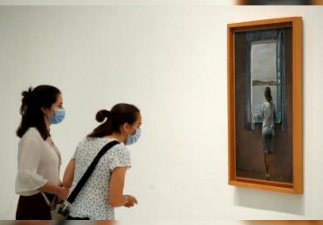 """Dos mujeres observan la obra """"Figura en una finestra"""" de Salvador Dalí en el museo Reina Sofía, este sábado, en su reapertura. EFE/ Chema Moya"""