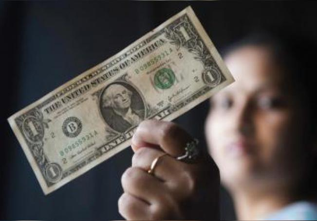 A photo illustration shows a woman holding up a US Dollar. EPA/JAGADEESH NV/File