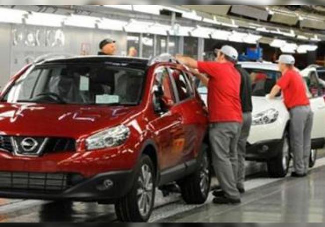 Trabajadores de Nissan ultimando unidades recién salidas de la línea de producción.