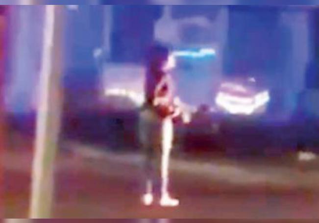 Imagen extraída del video que muestra a la mujer con el arma del uniformado.