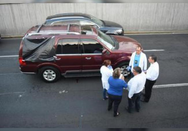 Fotografía que muestra a varios peritos forenses mientras inspeccionan el vehículo que fue abandonado en una vía rápida de Ciudad de México (México). En el interior del automóvil se hallaban dos hombres, uno sin vida y otro herido, presuntamente de nacionalidad colombiana.