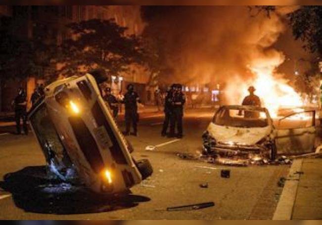 Agentes de policía tras dos coches incendiados durante una protesta el 31 de mayo de 2020, en Washington, por la muerte de George Floyd en Mineápolis.