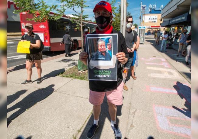 Fotografía del 4 de julio donde aparece Marco Mendicino sosteniendo un cartel con la imagen de Juan López Chaparro que ha muerto a consecuencia de COVID-19, durante una manifestación para reclamar que los jornaleros extranjeros puedan solicitar la residencia permanente en Toronto, Canadá. EFE/Julio César Rivas
