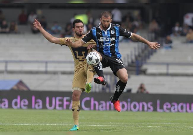 El jugador Luis Quintana (i) de Pumas disputa el balón con Emanuel Villa (d) de Queretaro. EFE/Alex Cruz/Archivo