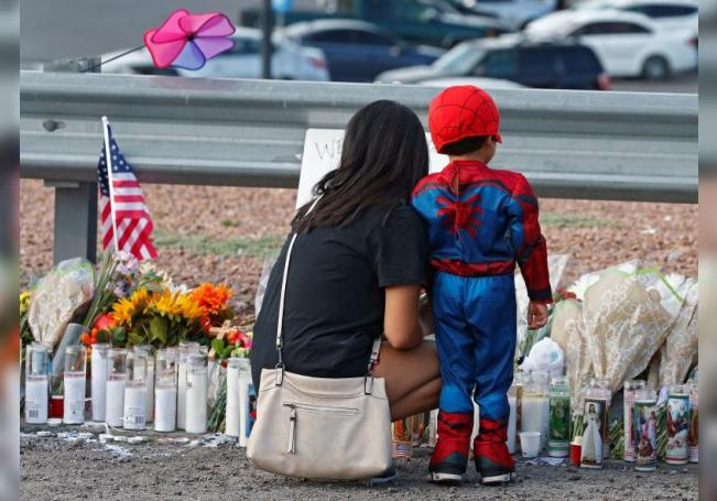 A woman and a young child pause while attending the make shift memorial along the street after the mass shooting that happened at a Walmart in El Paso, Texas, USA. EFE/EPA/LARRY W. SMITH/File