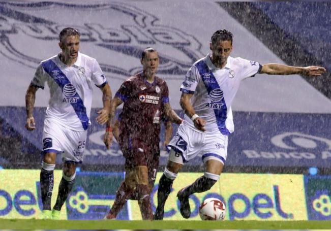 Los jugadores Maximiliano Perg (i) y Javier Salinas (d,) de Puebla, pelea por el balón con Milton Caraglio (c), de Cruz Azul, durante un juego de la segunda jornada del Torneo Guardianes 2020, del Fútbol Mexicano, este viernes en el estadio Cuauhtémoc de la Ciudad de Puebla (México). EFE/Hilda Ríos