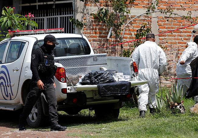 Miembros de la Fiscalía del Estado y peritos del Instituto Jalisciense de Ciencias Forenses (IJCF) trabajan este viernes, en una nueva fosa clandestina de la cual se han extraído 23 cuerpos