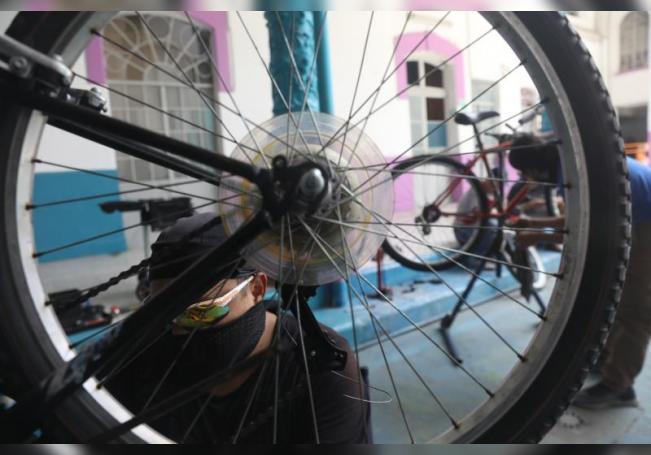 Fotografía de un voluntario de Bicitekas arreglando una bicicleta, este domingo, en Ciudad de México (México). EFE/Sáshenka Gutiérrez