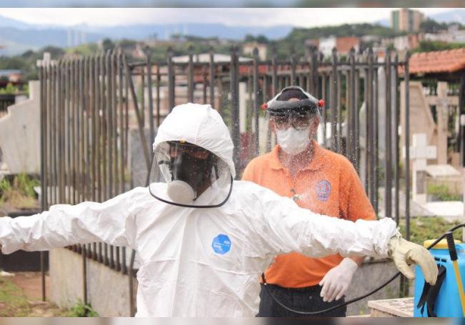 Trabajadores gubernamentales se desinfectan luego de enterrar un féretro con una víctima de covid-19 el 8 de agosto de 2020, en el cementerio de San Cristóbal, estado Táchira (Venezuela). EFE/ Johnny Parra