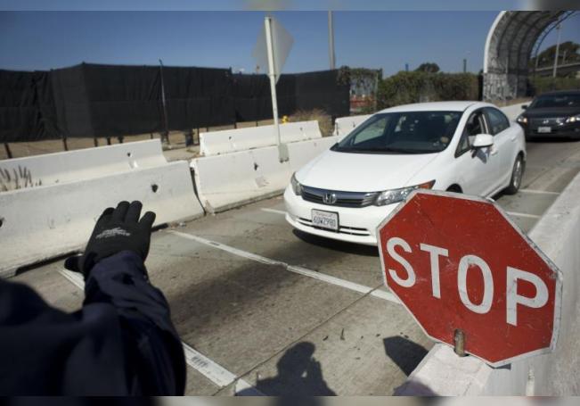 Un agente de la Oficina de Aduanas y Protección Fronteriza (CBP) de EE.UU ordena a un auto que se dirige a México a través del paso de San Ysidro (San Diego) -Tijuana (México), que pare para una inspección. EFE/DAVID MAUNG/Archivo