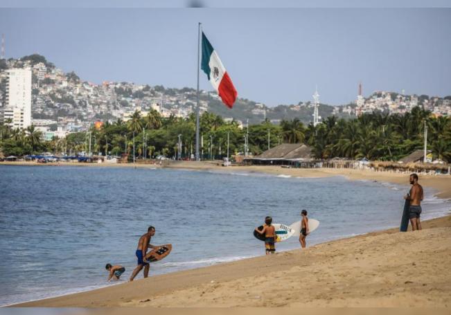 Fotografía fechada el 2 de junio de 2020 que muestra turistas mientras pasean por las playas del balneario de Acapulco. EFE/David Guzmán/Archivo