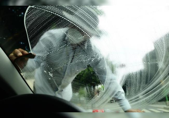 Jóvenes trabajan limpiando parabrisas en una calle de Ciudad de México (México). EFE/Jorge Núñez/Archivo