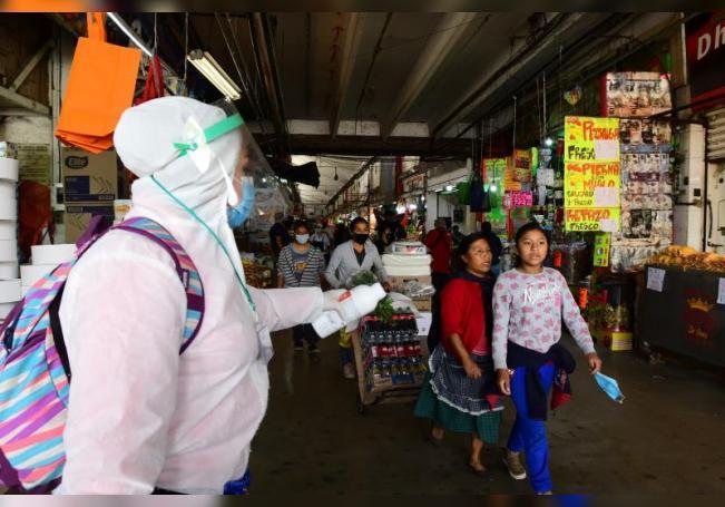 Una empleada de la Salud ofrece gel antibacterial a personas hoy en un mercado de Ciudad de México (México). EFE/Jorge Núñez